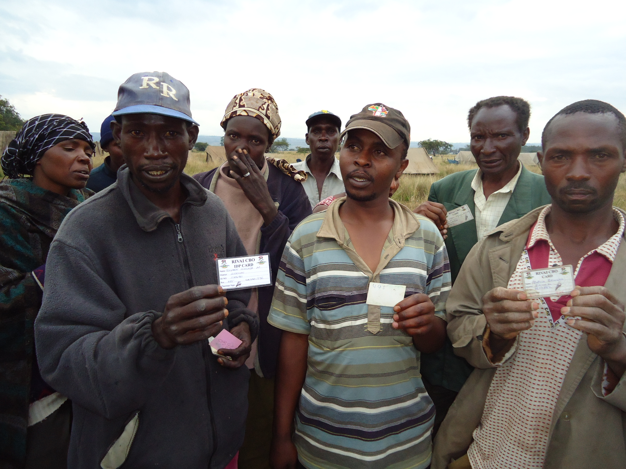 IDPs at GIWA farm showing their registration cards