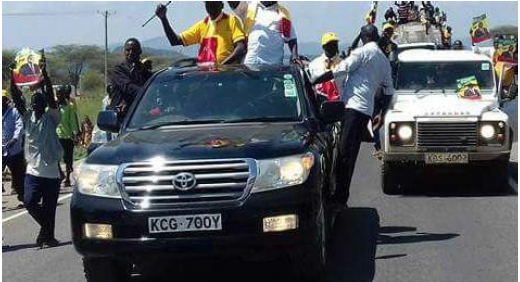 Image of official vehicle (white land rover) ferrying Jubilee supporters to a political rally. It belongs to Tiaty NG _CDF. Its official number plates (GK A 151G) which were replaced with civilian plates KBS 600Z on this occasion.